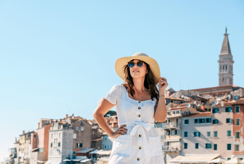 portrait-of-a-young-woman-in-white-dress-and-sun-hat-posing-in-front-of-a-picturesque-old-town-summer_t20_xXvv4l