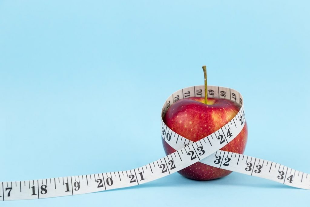 red-apple-wrapped-in-inch-tape-on-blue-color-background-symbolizes-weight-loss-free-space-for-text_t20_yXGVza