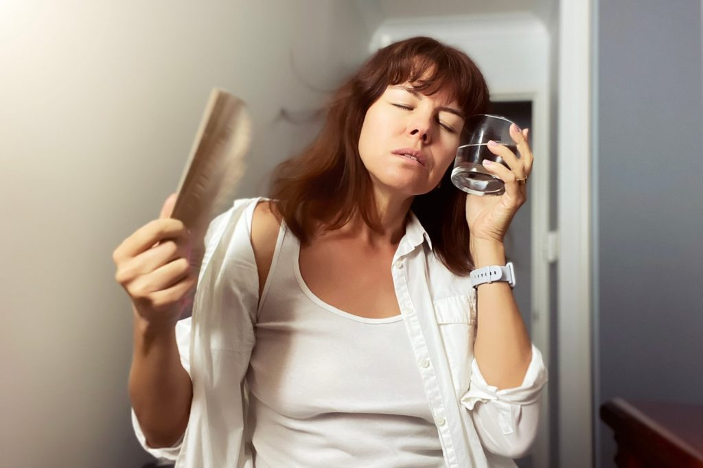 a-middle-aged-woman-cooling-down-with-a-fan-and-glass-of-water-to-relieve-the-symptoms-of-a-hot-flush_t20_zW347J
