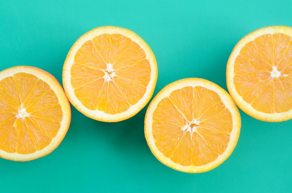 top-view-of-a-several-orange-fruit-slices-on-bright-background-in-turquoise-green-color-a-saturated_t20_wQv8Ar