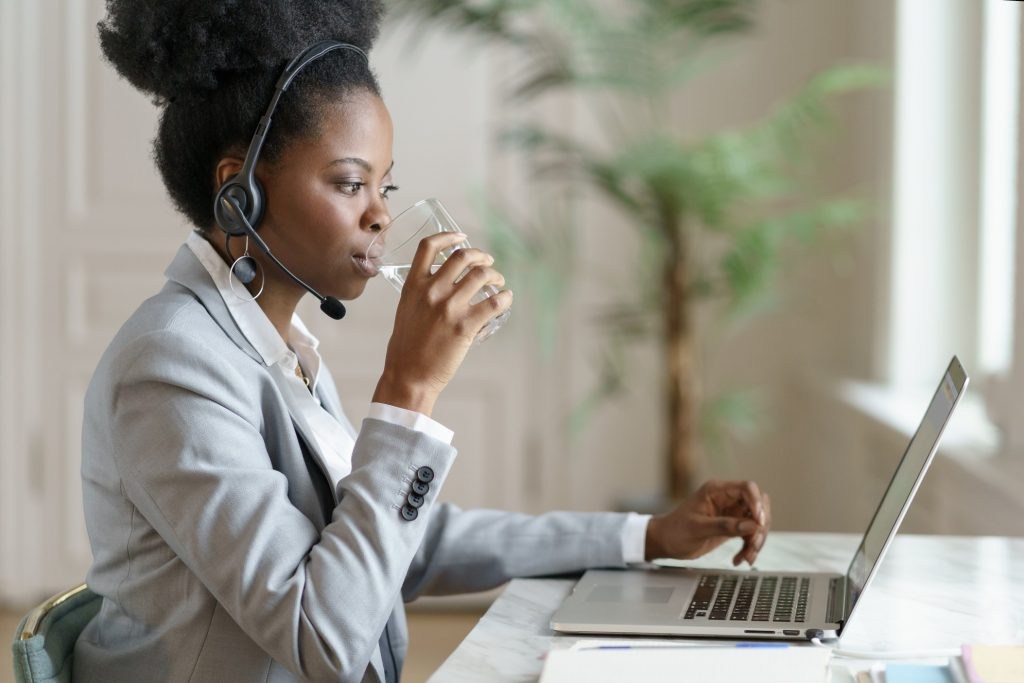 confident-afro-employee-woman-in-blazer-with-headphones-looking-at-laptop-screen-working-at-home_t20_E0yb3X